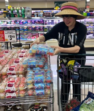 shopping \ Angelman Syndrome News \ Columnist Mary Kay's daughter, Jessie, grabs a package of blue unicorn cupcakes at the grocery store