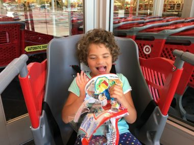 DIY projects and special needs products | Angelman Syndrome News | Columnist Sabrina Johnson's daughter, Juliana, sits in a Caroline's Cart at the supermarket. She holds her backpack and smiles
