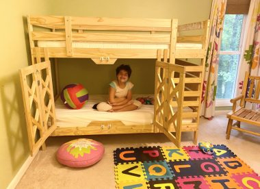 DIY projects and special needs products | Angelman Syndrome News | Juliana, 11, who has Angelman, sits cross-legged in a safety bunk bed her parents built. A natural wood color, the bed has two safety gates and a ladder, and sits in a colorful bedroom.