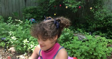 DIY projects and special needs products | Angelman Syndrome News | With her hair in a ponytail, Juliana, 11, wears a bandana bib her mom made as she plays outdoors with a beach ball