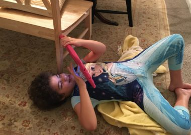regression \ Angelman Syndrome News \ The author's daughter Juliana, 11, lies on the floor playing with an iPad during some down time