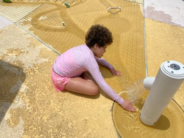 regression \ Angelman Syndrome News \ Juliana, 11, loves playing with water. Here she sits outdoors in a bright pink shirt and plays with water flowing from a large sprayer