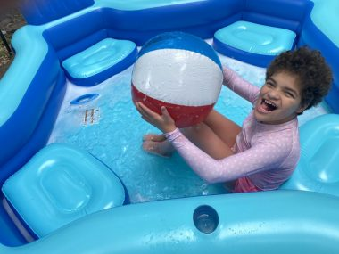 Juliana sits in her splash pool and holds an inflatable beach ball.