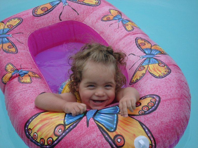 Juliana, pictured here as a toddler, smiles from a pink inflatable float with orange butterflies.