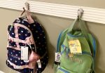 labels \ Angelman Syndrome News \ Photo of backpacks hanging from wall hooks. One is black and pink and one is green.