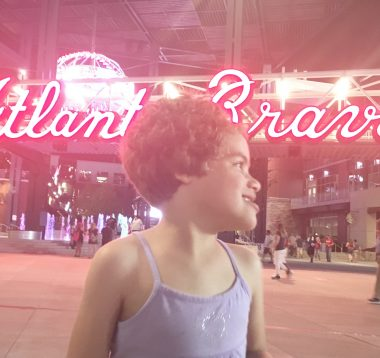 Staycation \ Angelman Syndrome News \ A nighttime shot of Juliana smiling in front of a glaring Atlanta Braves neon sign outside the ballpark.