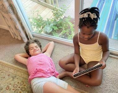 Homework \ Angelman Syndrome News \ Juliana relaxes on the carpeted floor of her house as her sister, Jessa, reads a story about having nice hands.