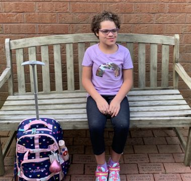 change \ Angelman Syndrome News \ Juliana sits on a bench, her school bag at her side, waiting to start fifth grade