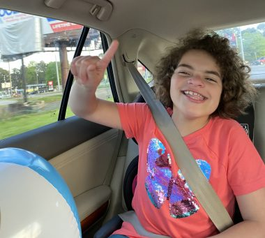 Staycation \ Angelman Syndrome News \ Buckled safely in the back seat of a car, Juliana smiles and raises her index finger as her family heads to a nearby hotel.