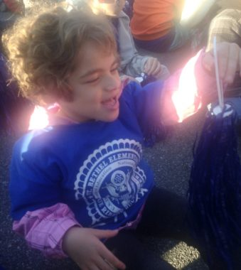 change \ Angelman Syndrome News \ A sunny photo shows Juliana in kindergarten, smiling and wearing a blue shirt with her school logo and holding a pompom