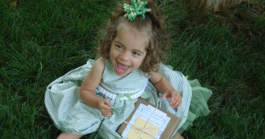Angelman child's happy demeanor | Angelman Syndrome News | Juliana sits on the grass in a pretty green dress with a green bow on her head while flashing a smile. She is opening a gift.