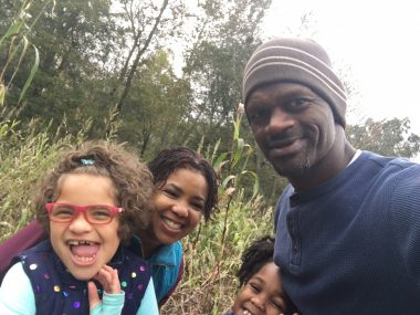 Angelman child's happy demeanor | Angelman Syndrome News | Juliana flashes a big smile and is accompanied by her mother, father, and sister in a wooded, outdoor area