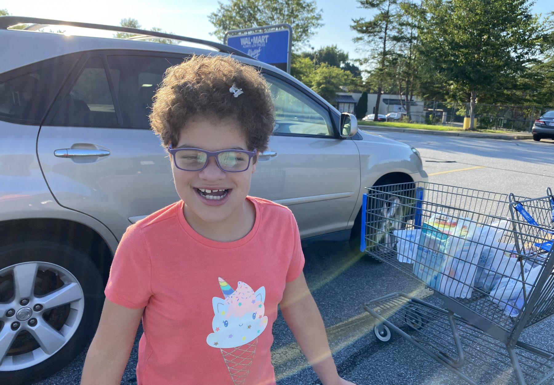 Outings with Angelman | Angelman Syndrome News | With a bright pink shirt and the sun behind her, Juliana smiles in a shopping center parking lot on an outing with her mom.