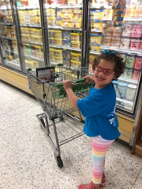 Outings with Angelman | Angelman Syndrome News | Managing cart skills with Angelman | Juliana smiles while pushing a cart at the