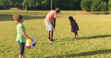 do-over | Angelman Syndrome News | Juliana stands on the golf course as her father explains the rules of the sport to her sister