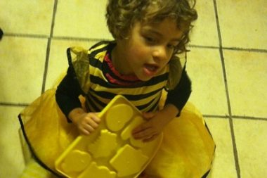 trick-or-treating with Angelman syndrome   Angelman Syndrome News   Juliana sits on the floor wearing a bumblebee costume before going trick-or-treating.